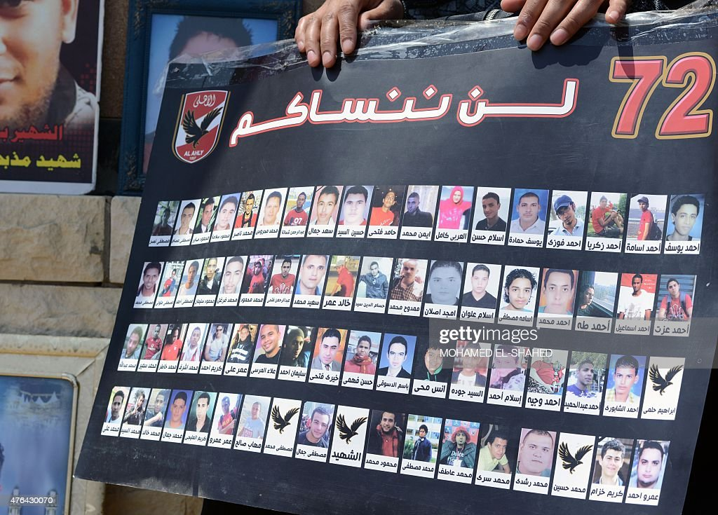 A picture taken on June 9 2015 shows a relative holding a poster with portraits of the victims of a February 2012 riot in the eastern city of Port...