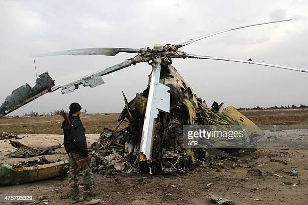 A picture taken on March 1 2014 rebel fighters inspecting the wreckage of a Syrian army helicopter after alQaedalinked group Islamic State of Iraq...
