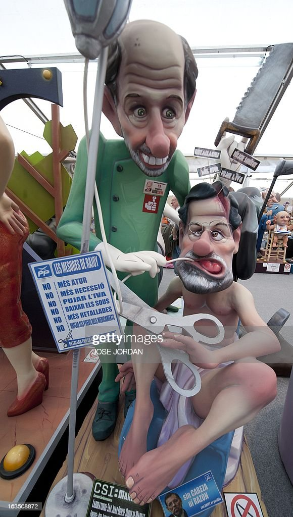 A picture taken on March 11, 2013 shows a Falla, a gigantic sculpted structure of cardboard and wood which humorously portrays relevant current events and personalities, caricaturing Spain's Prime Minister Mariano Rajoy and Spain's Socialist Party (PSOE) Alfredo Perez Rubalcaba, during an exhibition before preparations for the Fallas Festival, in Valencia. The Fallas will be burned in the streets of Valencia on March 19, 2013, as a tribute to St. Joseph, patron saint of the carpenters' guild. AFP PHOTO / JOSE JORDAN