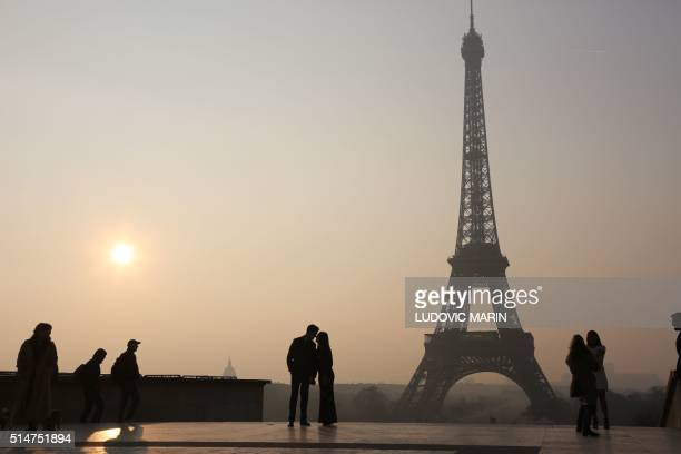 Picture taken on March 11 2016 in Paris shows people walking in front of the Eiffel tower at sunrise in Paris / AFP / LUDOVIC MARIN