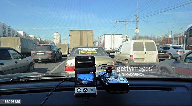 A picture taken on March 12 shows a mini camera with a screen placed on a dashboard of a car rolling a street in Moscow Dashboard video cameras are...