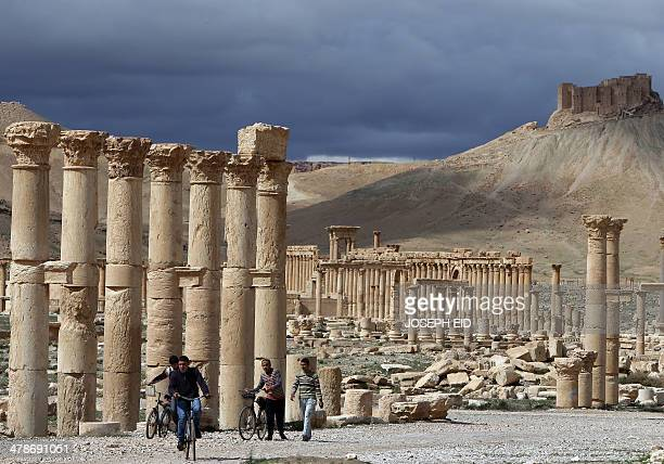 A picture taken on March 14 2014 shows Syrian citizens riding their bicycles the ancient oasis city of Palmyra 215 kilometres northeast of Damascus...
