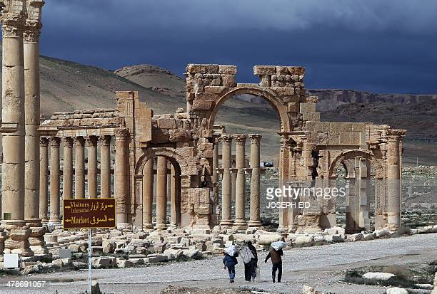 A picture taken on March 14 2014 shows Syrian citizens walking in the ancient oasis city of Palmyra 215 kilometres northeast of Damascus From the 1st...