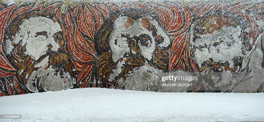 A picture taken on March 14, 2012, shows a fresco mosaic depicting Communist international leaders Friedrich Engels, Karl Marxand and Vladimir Lenin in the crumbling oval skeleton of the House of the Bulgarian Communist Party on mount Buzludzha in central Bulgaria. Over two decades after the toppling of the regime they glorified, the megalomaniac monuments of the communist era are still standing, setting a quandary for Bulgarian authorities, who can neither maintain nor dismantle them. AFP PHOTO / DIMITAR DILKOFF CULTURE