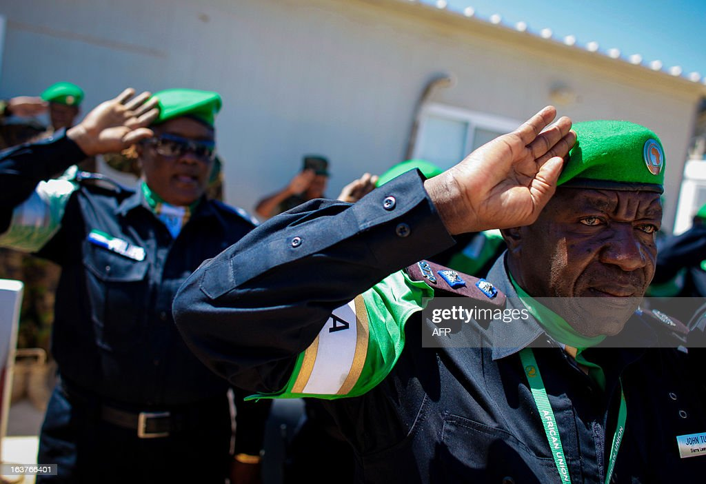 A picture taken on March 15, 2013 and released by the African Union-United Nations Information Support Team, shows officers from the Sierra Leonean Contingent serving with the African Union Mission in Somalia (AMISOM) Individual Police Officers (IPO) saluting during a medal parade at the AU Mission's headquarters in the Somali capital Mogadishu. 38 officers each received a 6-month Medal of Service today marking the mid-way point of their 1-year deployment to Somalia where they have been central in assisting the reforming restructuring, monitoring and mentoring of the Somali Police Force (SPF) as it begins rebuilding after two decades of conflict and instability in the Horn of Africa nation. AFP PHOTO / AU-UN IST / STUART PRICE