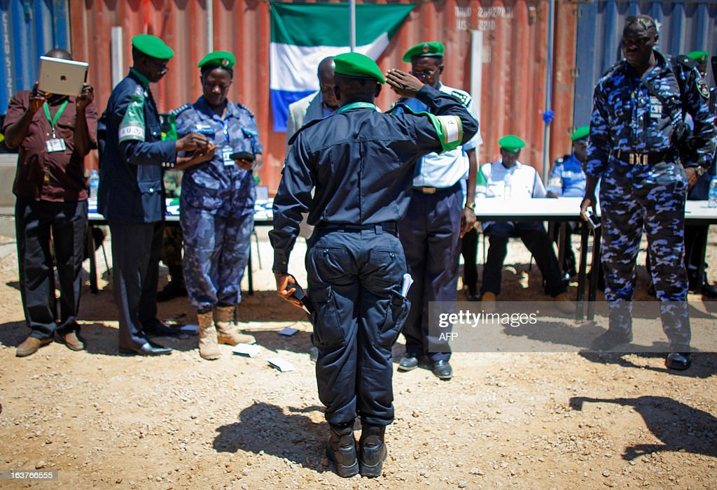 A picture taken on March 15, 2013 and released by the African Union-United Nations Information Support Team, shows an officer from the Sierra Leonean Contingent serving with the African Union Mission in Somalia (AMISOM) Individual Police Officers (IPO) saluting during a medal parade at the AU Mission's headquarters in the Somali capital Mogadishu. 38 officers each received a 6-month Medal of Service today marking the mid-way point of their 1-year deployment to Somalia where they have been central in assisting the reforming restructuring, monitoring and mentoring of the Somali Police Force (SPF) as it begins rebuilding after two decades of conflict and instability in the Horn of Africa nation. AFP PHOTO / AU-UN IST / STUART PRICE