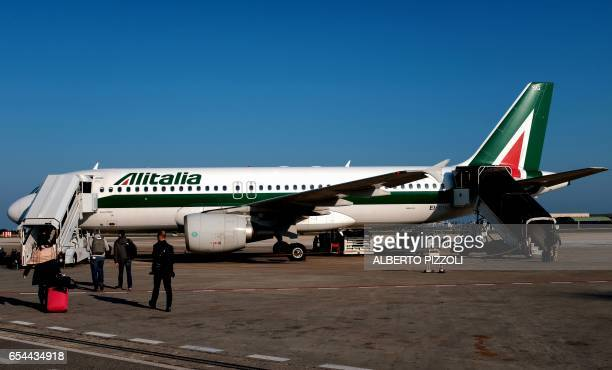 A picture taken on march 15 2017 show passengers as boarding an Alitalia Etihad plane on the runway of the airport of Brindisi The new company plan...