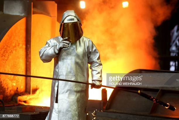 A picture taken on March 17 2017 shows a steel worker at German heavy industry giant ThyssenKrupp in Duisburg western Germany Thyssenkrupp unveiled...
