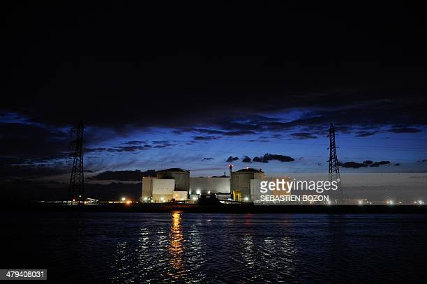 A picture taken on March 18 2014 in Fessenheim shows a view of the nuclear powerplant of Fessenheim by night Several dozen Greenpeace activists snuck...