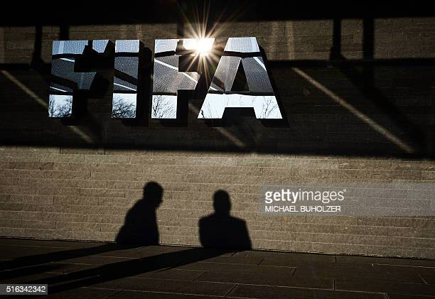 A picture taken on March 18 2016 shows men casting their shadow next to a FIFA logo at the FIFA headquarters in Zurich / AFP / MICHAEL BUHOLZER