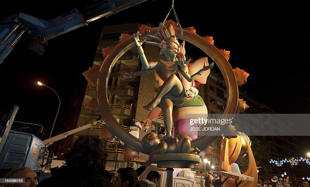A picture taken on March 19, 2013 shows a Falla, a gigantic sculpted structure of cardboard and wood which humorously portrays relevant current events and personalities, caricaturing elephant-headed Hindu god Lord Ganesha being dismantled after a man tried to immolate himself in front of the structure in Valencia. The Fallas will be burned in the streets of Valencia today, as a tribute to St Joseph, patron saint of the carpenters' guild.