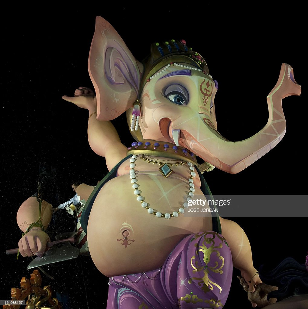 A picture taken on March 19, 2013 shows a Falla, a gigantic sculpted structure of cardboard and wood which humorously portrays relevant current events and personalities, caricaturing elephant-headed Hindu god Lord Ganesha being dismantled after a man tried to immolate himself in front of the structure in Valencia. The Fallas will be burned in the streets of Valencia today, as a tribute to St Joseph, patron saint of the carpenters' guild. AFP PHOTO / JOSE JORDAN