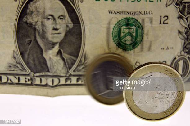 A picture taken on March 2 2010 in Paris shows one euro coins displayed in front of a one dollar note The euro slumped to its lowest level in more...