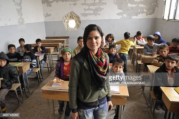 A picture taken on March 2 2015 shows a teacher posing for a picture while pupils attend the first day of school in the Syrian Kurdish town of Kobane...