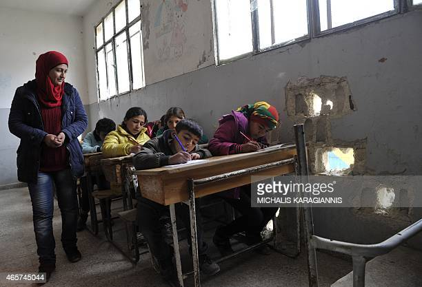 A picture taken on March 2 2015 shows pupils attending the first day of school in the Syrian Kurdish town of Kobane also known as Ain alArab as they...