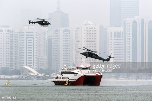 A picture taken on March 2 2017 in Abu Dhabi shows Emirati military helicopters performing during the 'Union Fortress Live Military Demonstration'...