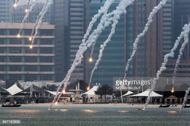 A picture taken on March 2 2017 in Abu Dhabi shows flares falling by the Abu Dhabi corniche during the 'Union Fortress Live Military Demonstration' /...