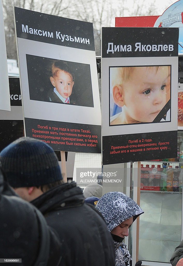 A picture taken on March 2, 2013, shows people rallying in Moscow with the portraits of the Russian children who died in USA after being adopted there. The signs under the portraits read (L-R): Maxim Kuzmin, Dima Yakovlev. Thousands of people, including activists from pro-Kremlin children's advocacy groups, marched that day through Moscow urging authorities to ban all foreign adoptions. Russia said today it was seriously concerned by a US decision not to prosecute the adoptive parents of a Russian boy, Max Shatto -- born Maxim Kuzmin, whose January death has sparked a diplomatic row between the two countries. AFP PHOTO / ALEXANDER NEMENOV