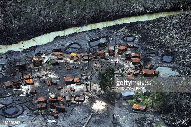 A picture taken on March 22 2013 shows an illegal oil refinery destroyed by Joint Task Force at Nembe Creek in the Niger Delta on March 22 2013 Shell...
