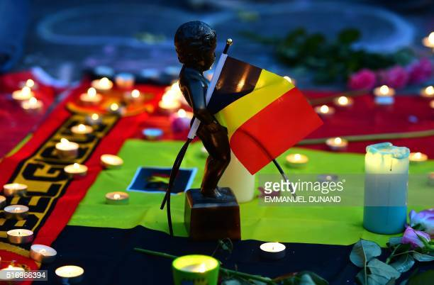 A picture taken on March 22 2016 in Brussels shows a replica of the Manneken Pis statue holding the Belgium flag at a makeshift memorial in tribute...