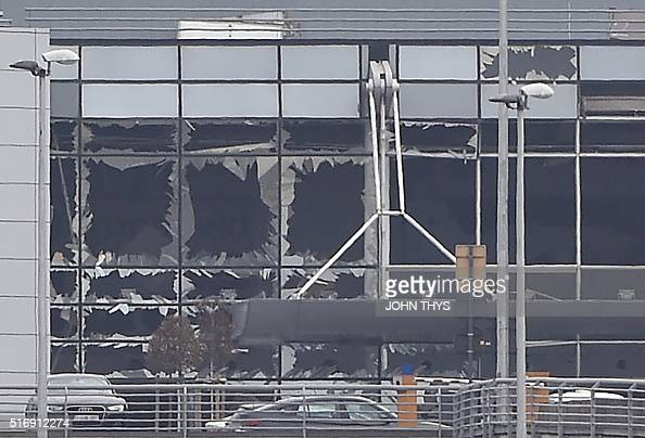 A picture taken on March 22 2016 in Zaventem shows the damaged facade of Brussels airport after at least 13 people were killed and 35 injured as twin...