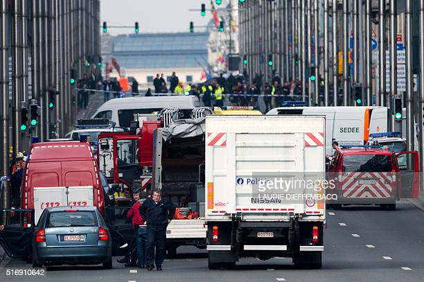 A picture taken on March 22 2016 shows Belgian police and emergency staff arriving in the Wetstraat Rue de la Loi which has been evacuated after an...