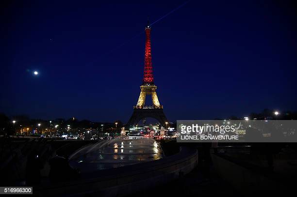 A picture taken on March 22 2016 shows the Eiffel Tower in Paris illuminated in colours of the Belgian flag in tribute to the victims of terrorist...