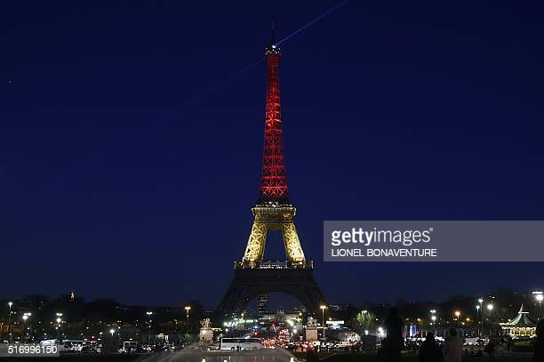 TOPSHOT A picture taken on March 22 2016 shows the Eiffel Tower in Paris illuminated in colours of the Belgian flag in tribute to the victims of...