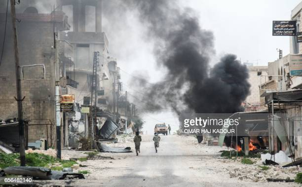 TOPSHOT A picture taken on March 22 2017 in the Syrian town of Tayyibat alImam in the countryside of the central province of Aleppo shows fighters...