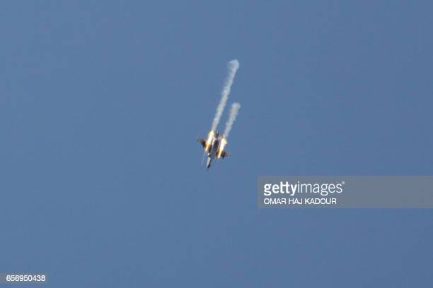 TOPSHOT A picture taken on March 23 shows a Syrian army jet firing rockets over the village of Rahbet Khattab in the Hama province Jihadists and...