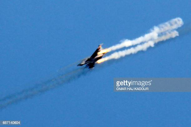 A picture taken on March 23 shows a Syrian army jet firing rockets over the village of Rahbet Khattab in the Hama province Jihadists and allied...