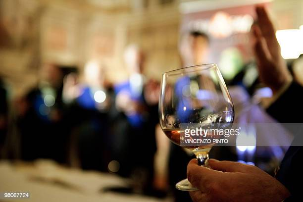 Picture taken on March 24 2010 shows a man with a glass of Armagnac during a ceremony in Rome after a copy of the 1531's Armagnac original product...