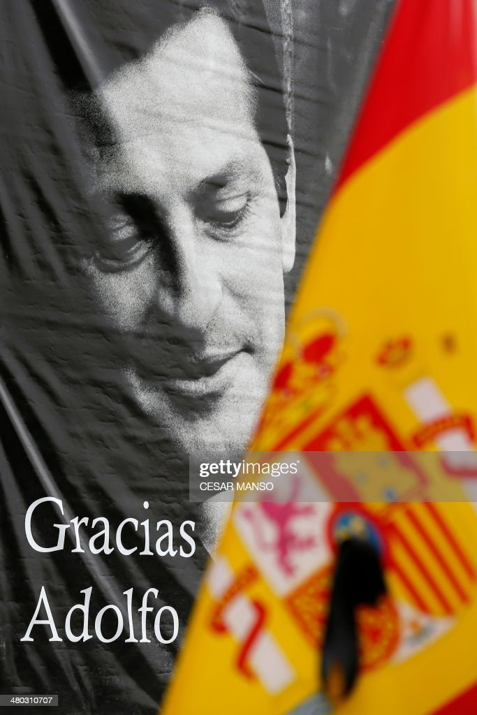 A picture taken on March 24, 2014 shows a portrait of former Spanish Prime Minister Adolfo Suarez behind a Spanish flag at the museum 'Adolfo Suarez y la transicion' (Adolfo Suarez and the transition) in Cebreros, Avila province. Adolfo Suarez, the prime minister who led Spain to democracy after decades of dictatorship and became its first elected premier after the death of General Francisco Franco, died on March 23 aged 81.
