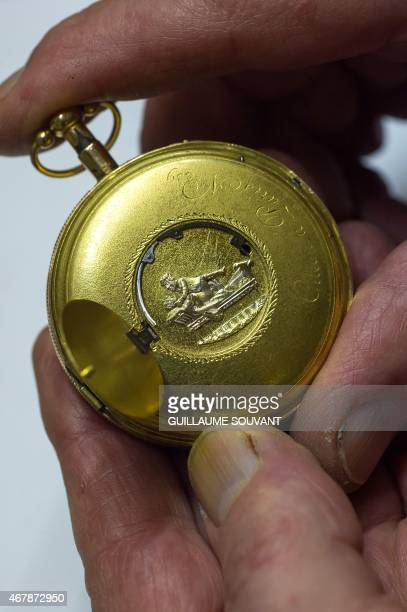 A picture taken on March 24 2015 in Orleans central France shows a close up of a model of a unique gold watch named 'coquine' on which a small hatch...