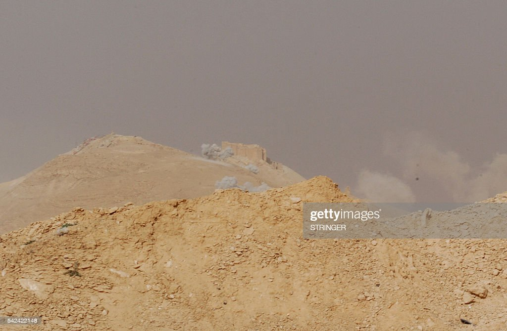 A picture taken on March 24 shows smoke rising close to the Palmyra castle also known as Palmyra citadel during shelling by Syrian troops on the...