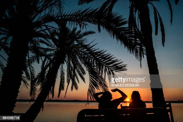 A picture taken on March 25 2017 shows a couple watching the sunset at Fatnas lake in the Egyptian desert oasis of Siwa some 560 kms west of Cairo...