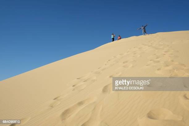 A picture taken on March 25 2017 shows people on a sand dune in the Egyptian desert oasis of Siwa some 560 kms west of Cairo and 55 kms to the Libyan...