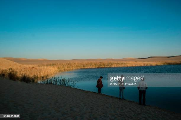 A picture taken on March 25 2017 shows people standing by a lake in the Egyptian desert oasis of Siwa some 560 kms west of Cairo and 55 kms to the...