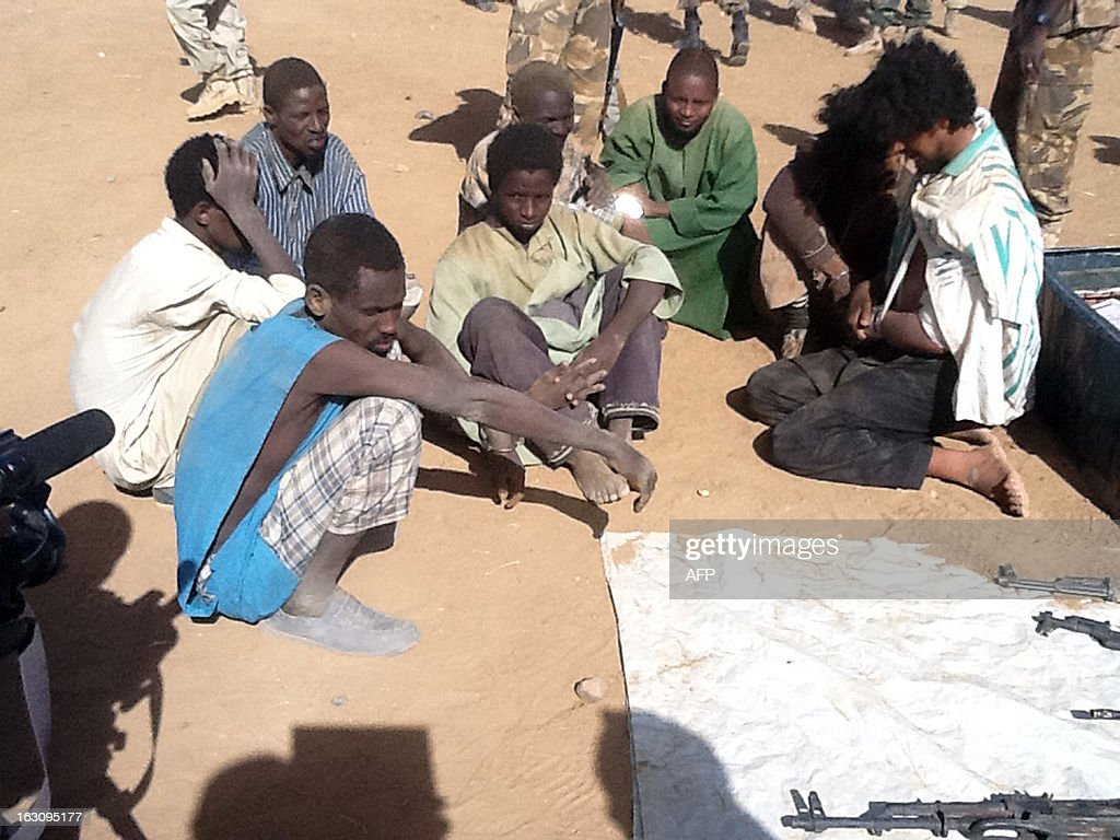 A picture taken on March 3, 2013 in Tessalit area shows alleged Islamist militants detained by the Chadian army after violent clashes in the Ifoghas mountains, northern Mali. Chad says its troops in northern Mali have killed Mokhtar Belmokhtar, the one-eyed Islamist leader who masterminded an assault on an Algerian gas plant in January that left 37 foreign hostages dead. The announcement came amid continued fighting in the mountains of northern Mali, where France on Sunday said a third French soldier had been killed since it launched operations against Islamist rebels in mid-January. AFP PHOTO / ALI KAYA