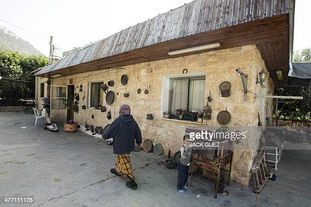 A picture taken on March 3 2014 shows a woman walking past a house belonging to the Abu Abbas family in the coastal city of Haifa in the north of...