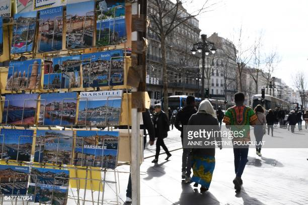 A picture taken on March 3 2017 in Marseille southern France shows people walking past postcards on the street Canebiere The street Canebiere...