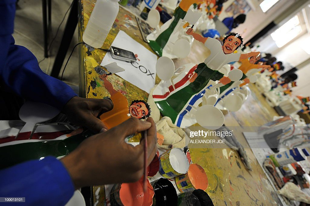 A picture taken on March 4, 2010 shows an employee as he paints the face of a football player onto a hardhat known as 'Makarapas' in Johannesburg. The 'Makarapas', a decorated plastic hard hat due to be settled on supporters' heads, are created by fans who carve shapes into the hats and adorn them with team colours, a process that can take four days to complete. As the world prepares for Africa's first World Cup, interest is growing in the continent, especially since the governing body FIFA ordered 2,000 Makarapas for twelve of the top teams from Wygers' factory in downtown Johannesburg. The Makarapa is, with the vuvuzela trumpet, an important part of the local football matches' festival atmosphere. Makarapas are miner hats modified and decorated in the colors of the team.