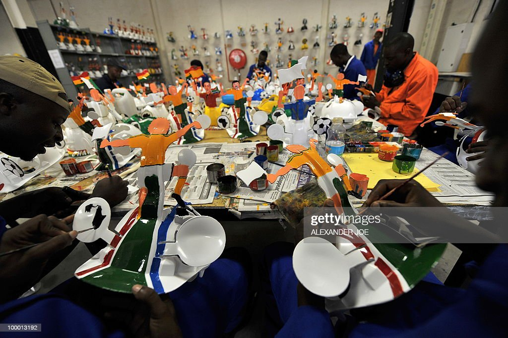 A picture taken on March 4, 2010 shows employees preparing a football player on a hardhat known as 'Makarapas' in Johannesburg. The 'Makarapas', a decorated plastic hard hat due to be settled on supporters' heads, are created by fans who carve shapes into the hats and adorn them with team colours, a process that can take four days to complete. As the world prepares for Africa's first World Cup, interest is growing in the continent, especially since the governing body FIFA ordered 2,000 Makarapas for twelve of the top teams from Wygers' factory in downtown Johannesburg. The Makarapa is, with the vuvuzela trumpet, an important part of the local football matches' festival atmosphere. Makarapas are hand-cut and hand painted miner hard hats in the colours of a team.