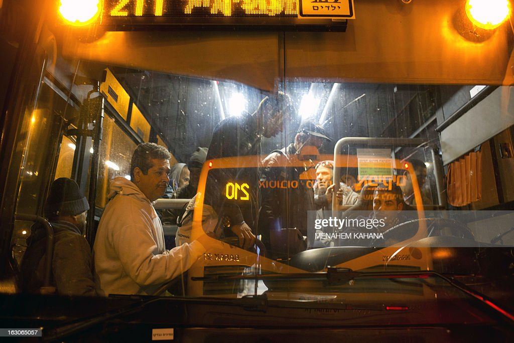 A picture taken on March 4, 2013 shows behind a window Palestinians boarding a bus as a new line is made available by Israel to take Palestinian labourers from the Israeli army crossing Eyal, near the West Bank town of Qalqilya, into the Israeli city Tel Aviv,.Thousands of Palestinians enter Israel to work every day after receiving permits, many of them in private vans. The new line will not be available for Jewish settlers. AFP PHOTO / MENAHEM KAHANA