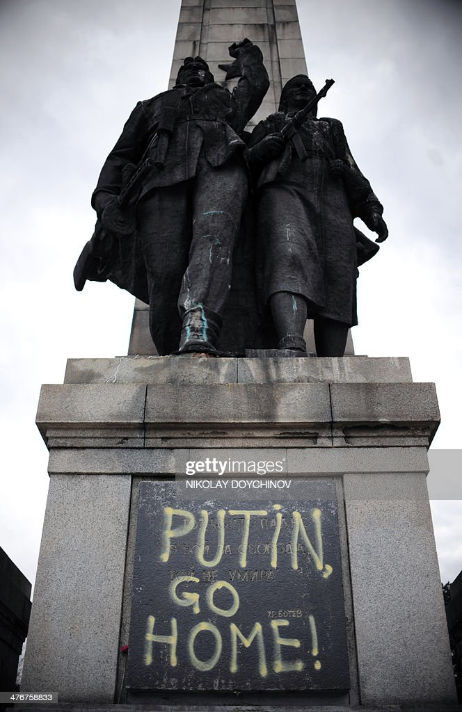 A picture taken on March 5, 2014 shows a monument of Communist soldiers in central Sofia. The Communist era monument was painted overnight in Ukrainian and Polish national flag colours with texts reading 'Putin go home!' ,'Crimea 2014' and 'Katyn 5.03.1940'.