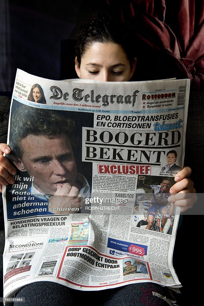 A picture taken on March 6, 2013 in Rotterdam shows a woman holding a copy of Dutch daily newspaper De Telegraaf dated March 6, reading 'Boogerd confesses' on its front page and showing a portrait of former Dutch cyclist Michael Boogerd who confessed to have used doping during his career. Boogerd said in an exclusive interview to De Telegraaf newspaper published on March 6 that he has been using EPO, blood transfusions and cortisone from 1997 until the end of his career in 2007. AFP PHOTO / ANP ROBIN UTRECHT -- netherlands out --