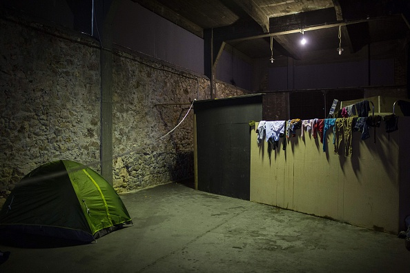 A picture taken on March 6, 2016 shows a general view of a makeshift migrant and refugee camp inside a building at the Piraeus harbour in Athens. At least 25 migrants including children died on Mar...