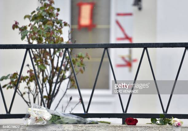 A picture taken on March 7 2017 in Orvault western France shows a bunch of flowers and roses laid in front of the entrance of the house of the...