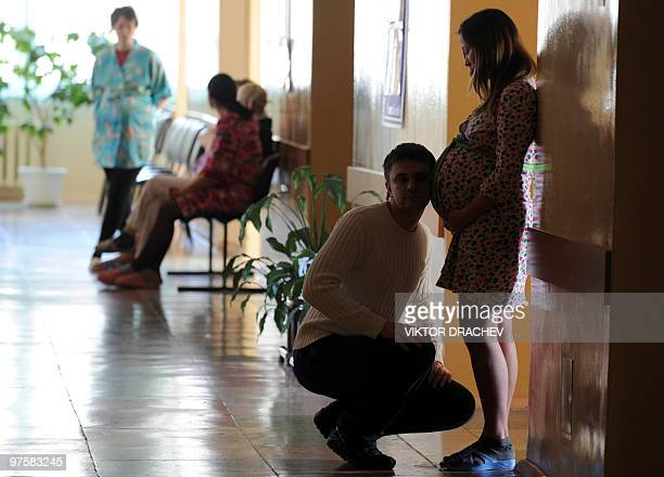Picture taken on March 8 2010 shows a Belarussian man putting his ear to a pregnant woman's belly in the maternity ward of a hospital in Minsk The...