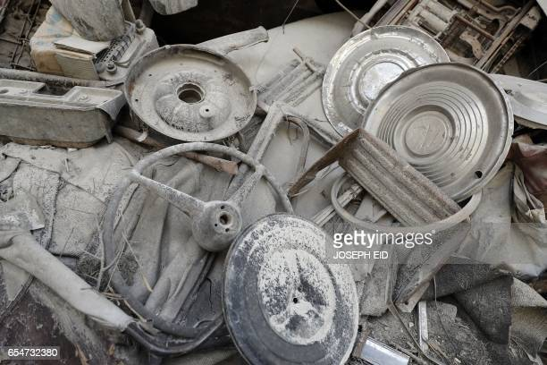 A picture taken on March 9 shows a hubcaps and steering wheels in the garden of Mohammed Mohiedin Anis or Abu Omar's home in Aleppo's formerly...